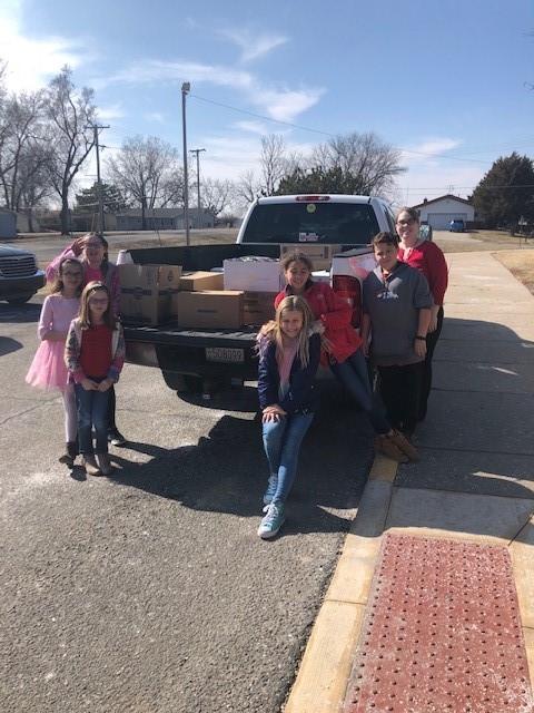 """Students stand outside of Milford Elementary celebrating the huge donation of canned goods they will be donating to the """"Wheels of Hope""""."""